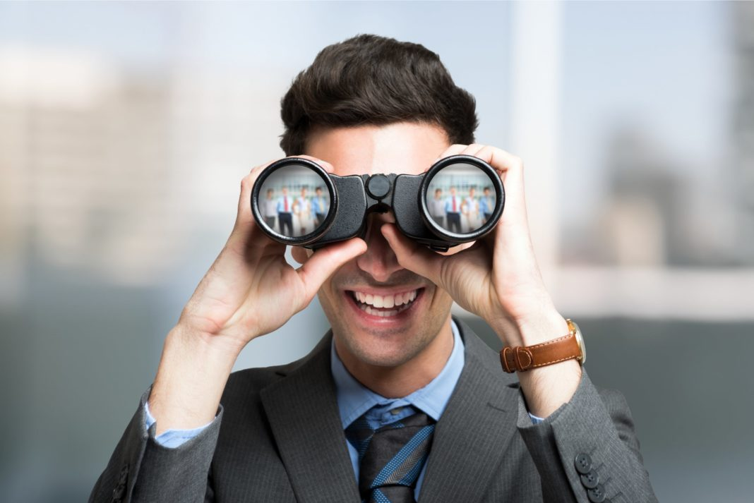 Businessman In Suit Searching For Job Candidates Using Binoculars