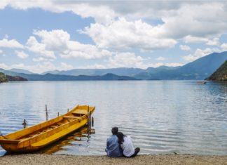 Young Couple Sitting On Beach Looking At Lugu Lake China