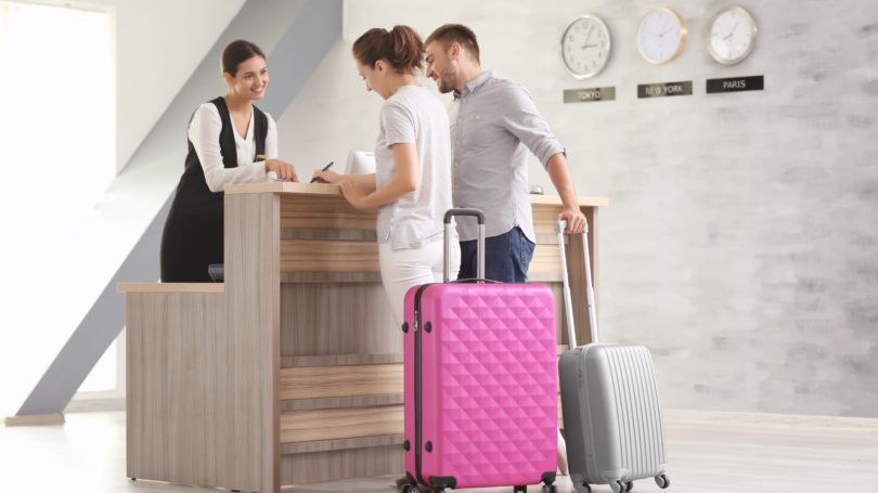 Couple Checking Into Hotel Luggage