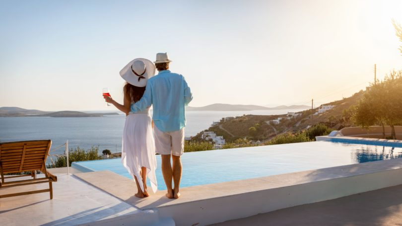 Couple Standing By The Infinity Pool