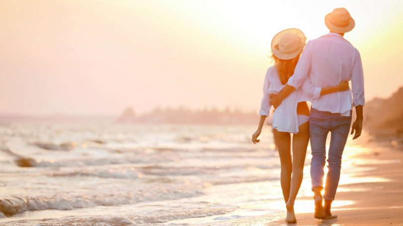 Couple Taking Long Walk On The Beach Golden Hour