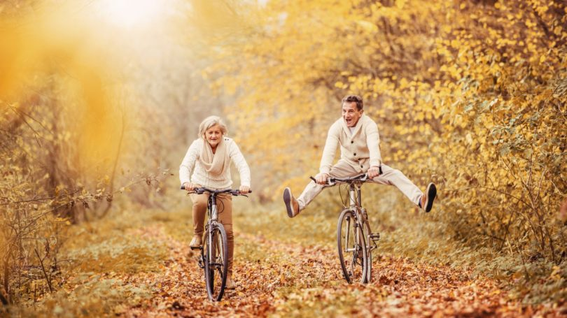 Elderly Couple Biking Through Foliage Trail Fall