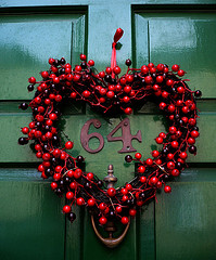 Heart shaped wreath of cranberries on a green door