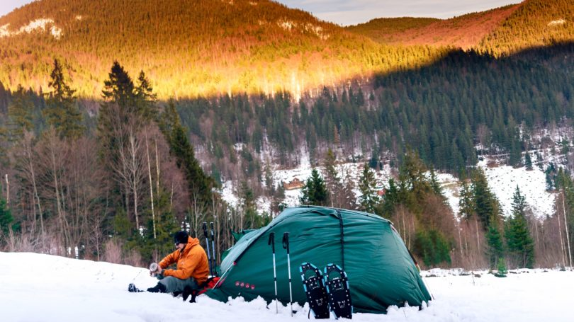 Man Camping Outside In The Snow Mountains Tent