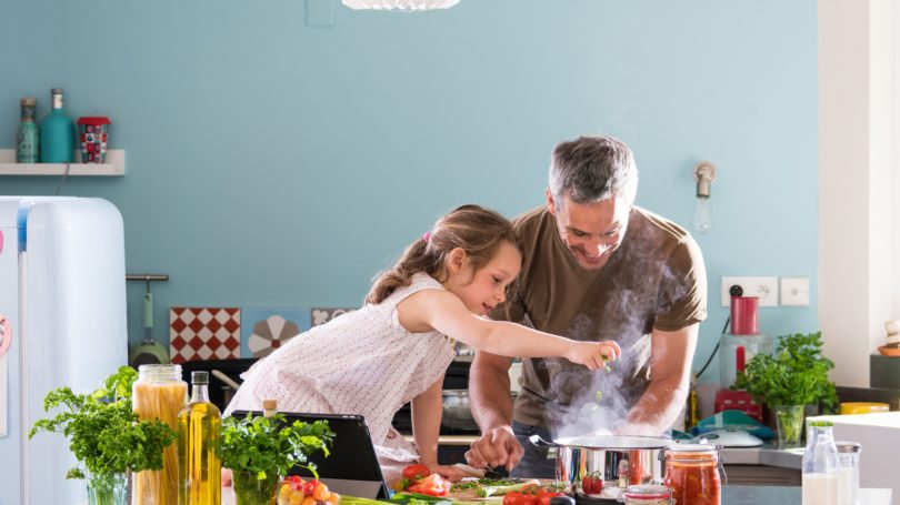 Father Daughter Cooking In Kitchen Stove Vegetables