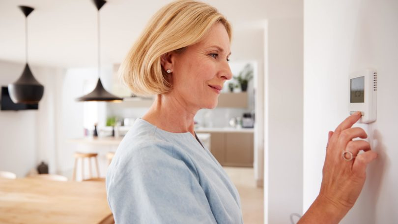 Older Woman Adjusting Thermostat At Home Kitchen