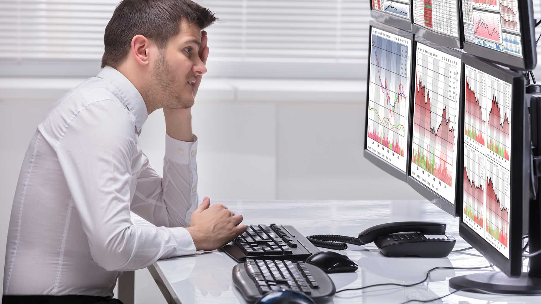stressed young man operator looking at graphs on computer screens