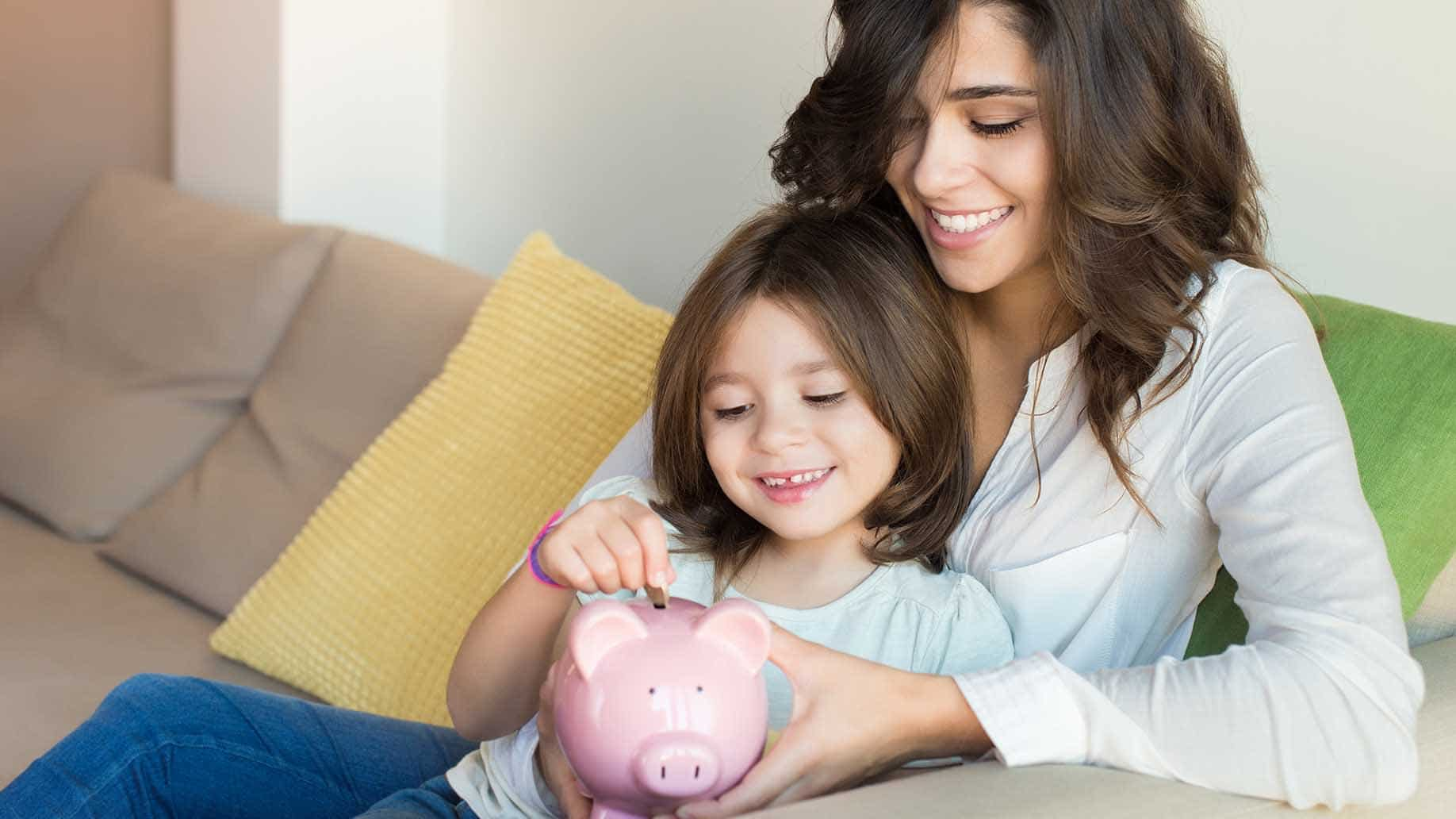mother daughter putting coins into a piggy bank
