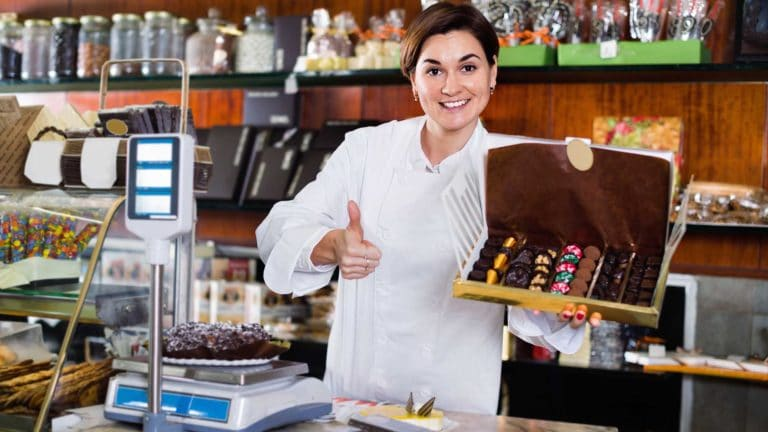 young woman offering large box of chocolates in confectionery