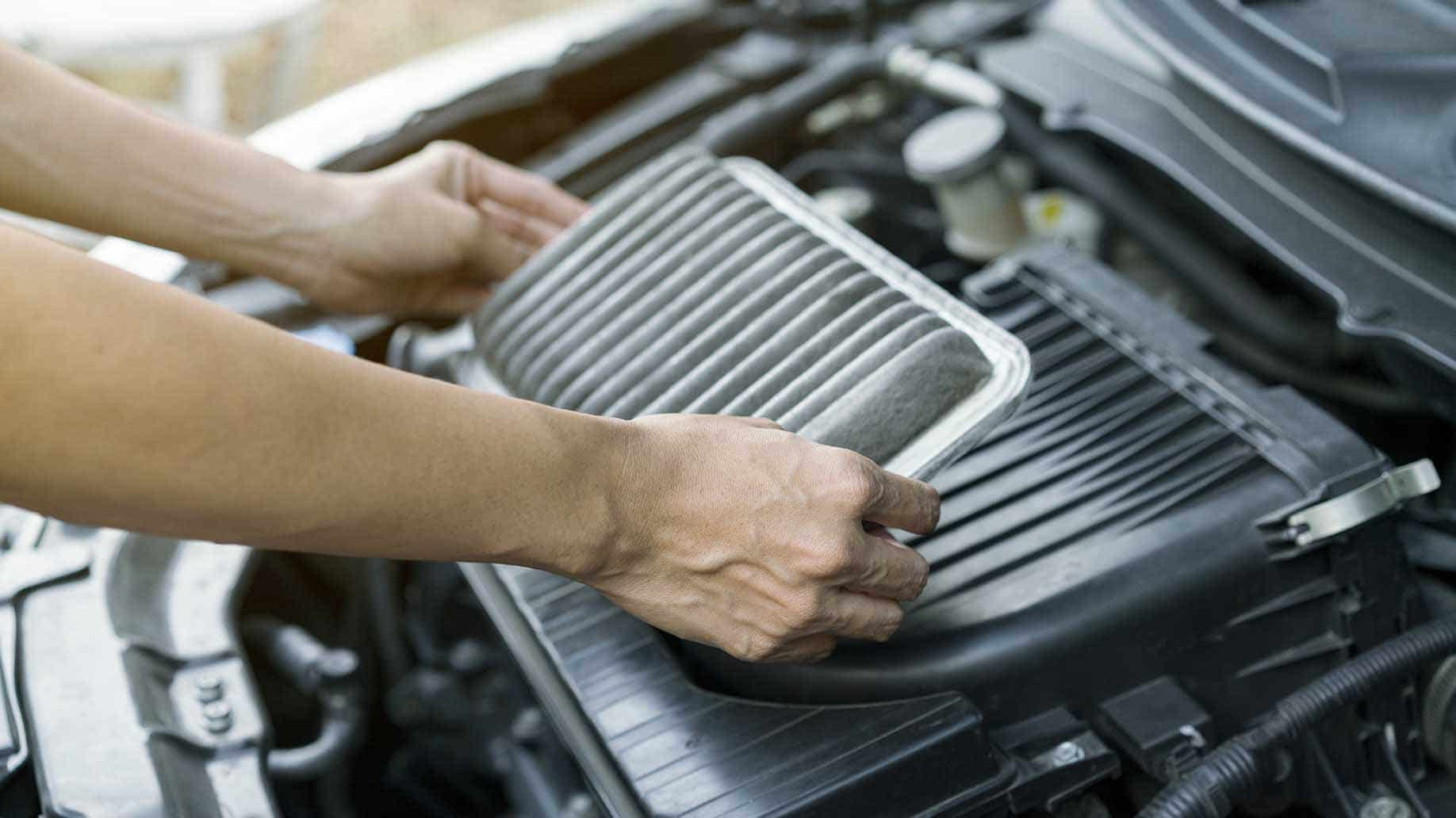 technician holding dirty car air filter