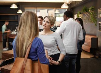 woman listening with concern to friend in busy cafe