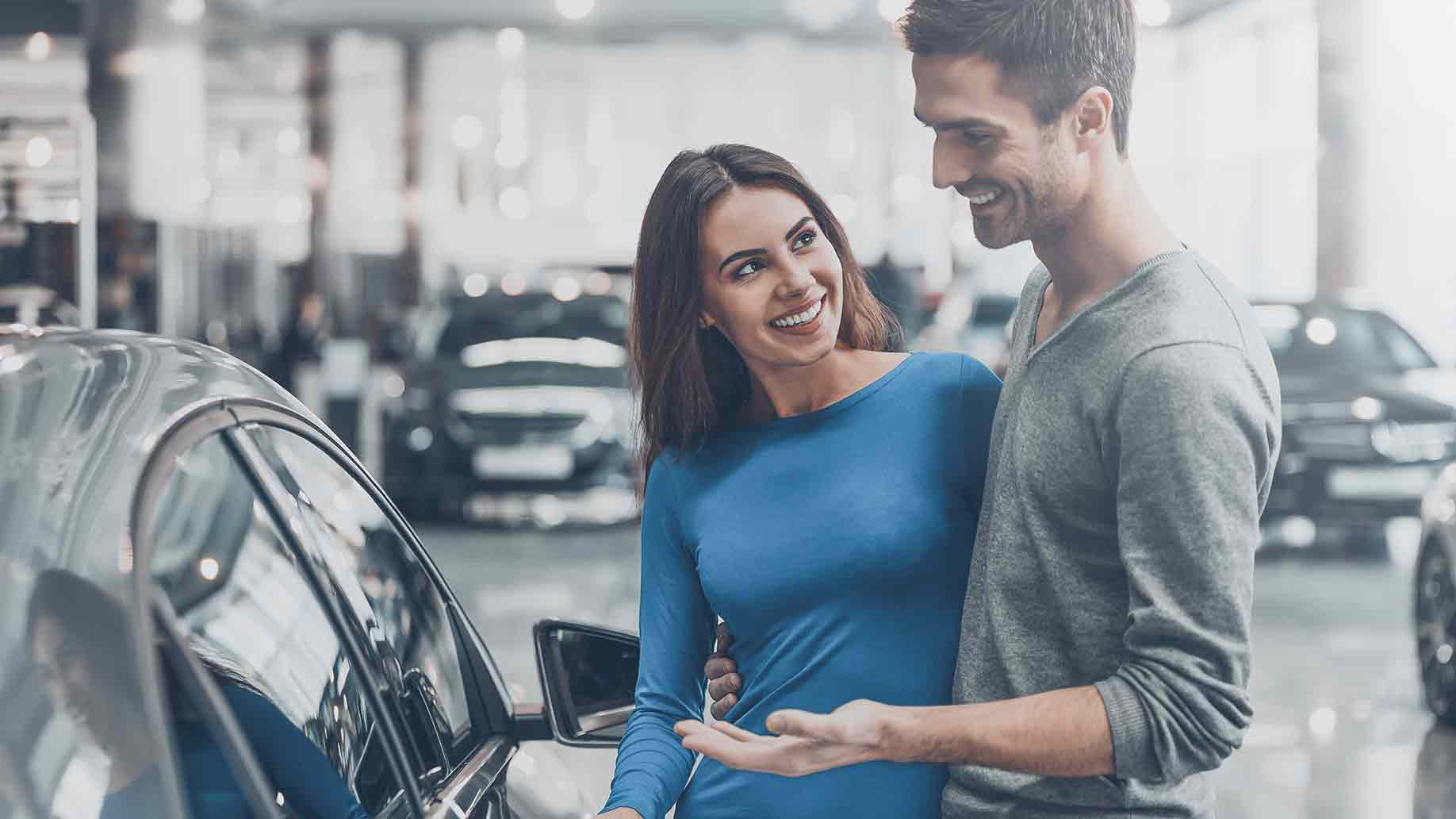 beautiful young couple standing at the dealership choosing car