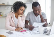Couple Looking At Bills To Pay Stressed