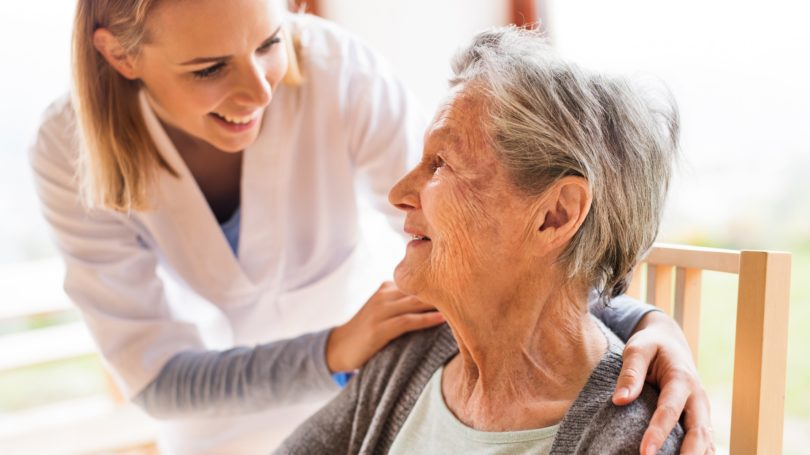 Elderly Woman Sitting Nurse Greeting Her