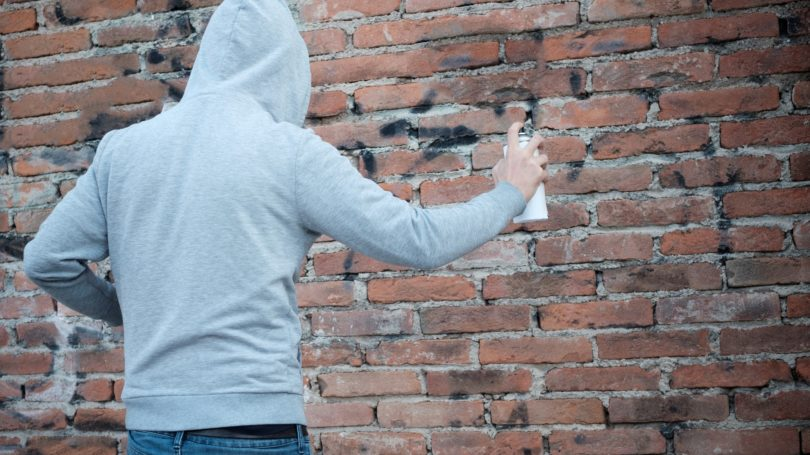 Man Writing Vandalism Graffiti Brick Wall