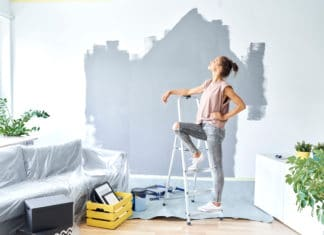 Woman Standing Ladder Half Painted Wall
