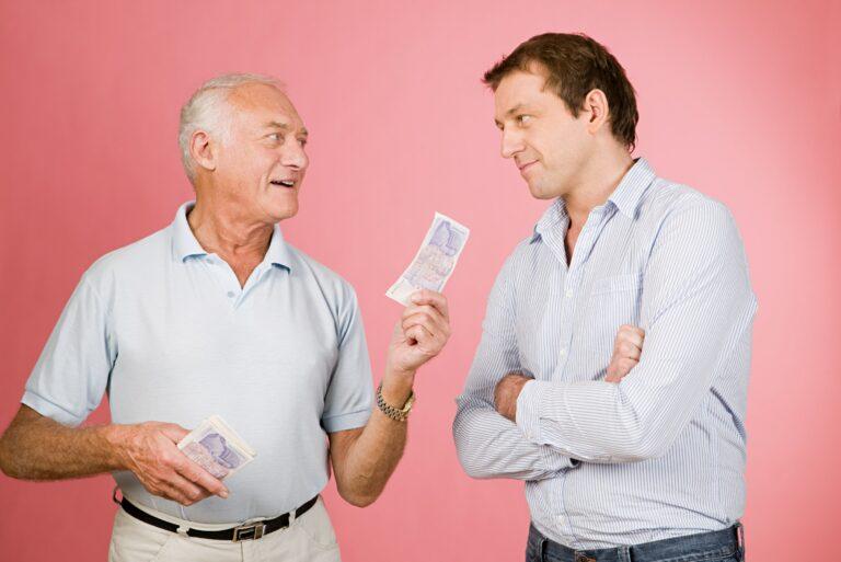 Elderly Man Lending Cash Younger Man