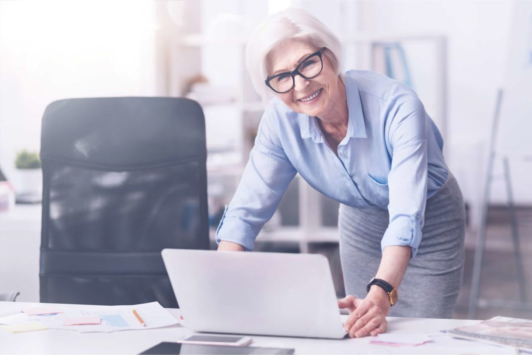 Older Woman Working In Office Smiling Retirement