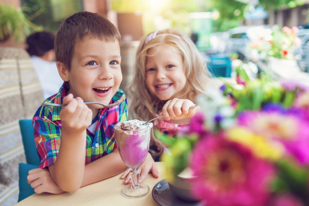 Little Boy And Girl Eating Icecream At Restaurant Al Fresco Spring