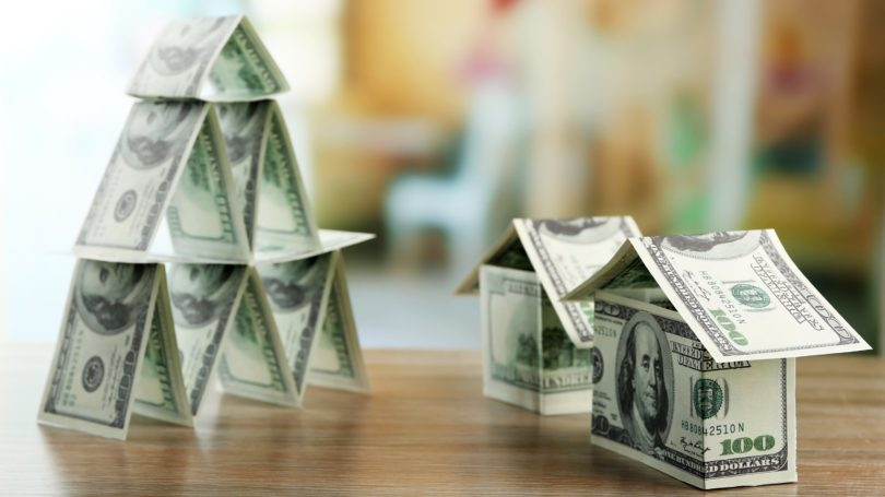 Money Cash Pyramids Houses On Wooden Table
