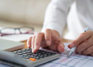 Womans Hands Reviewing Budget Calculator
