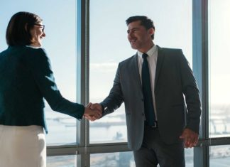 businessman businesswoman shaking hands together while?