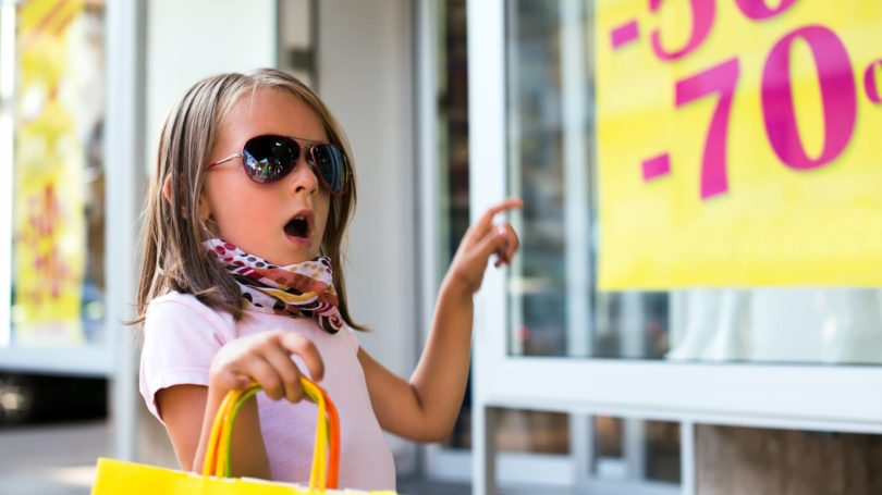 Excited Girl Pointing At Sale Sign Clearance Shopping