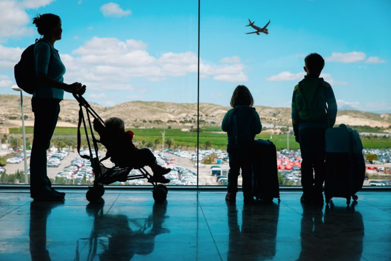 Mother Traveling With Infant And Toddlers At Airport