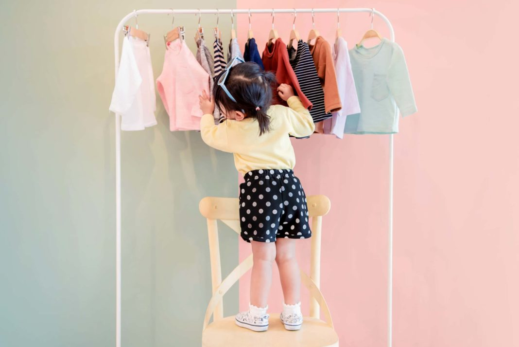 Toddler Girl Sorting Through Her Clothes Rack Stylish