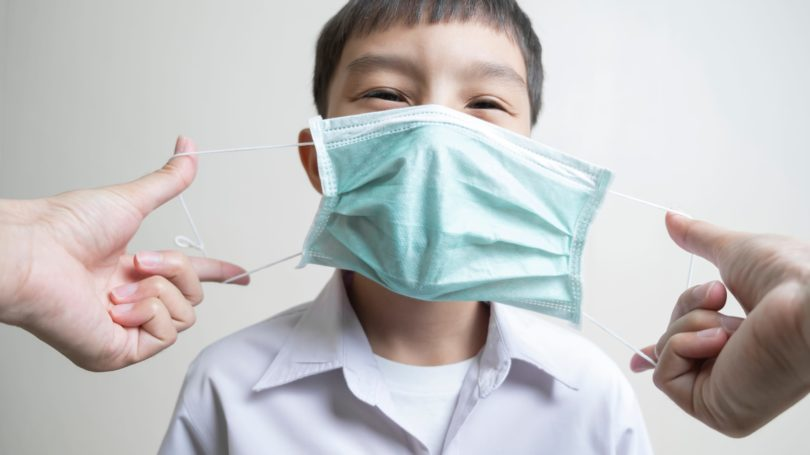 Adulting Putting On Mask For Student Boy