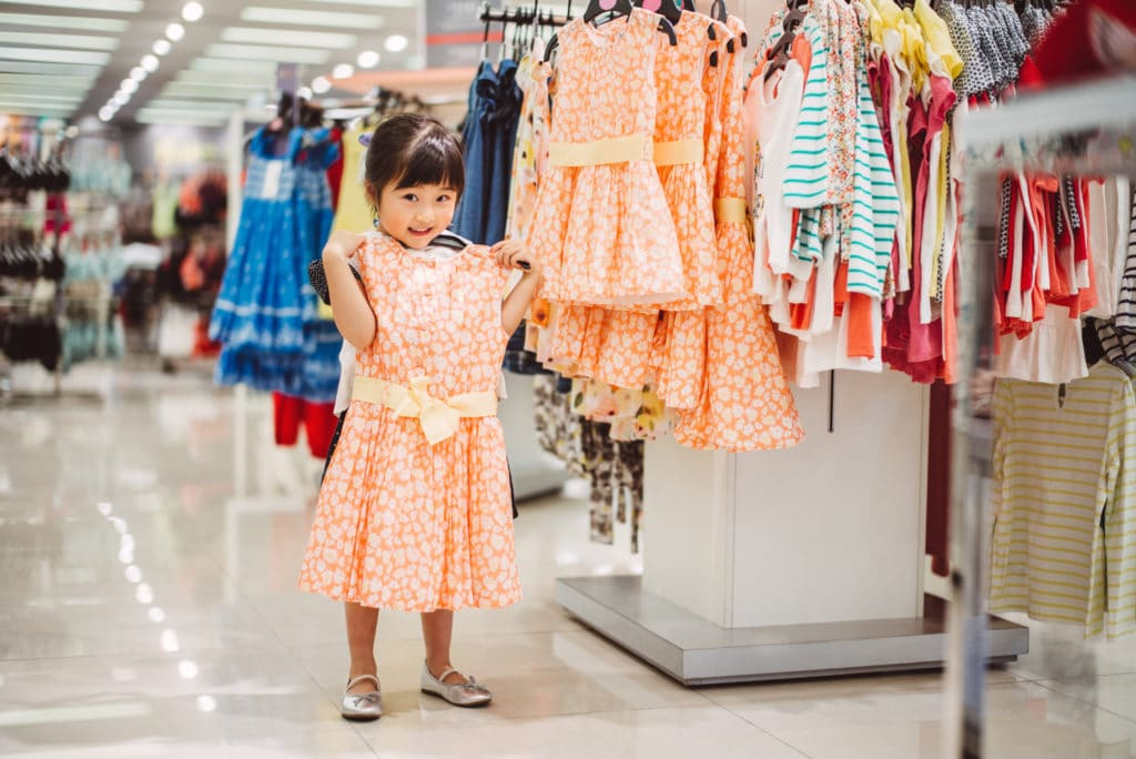 Young Girl Holding Dress Department Store