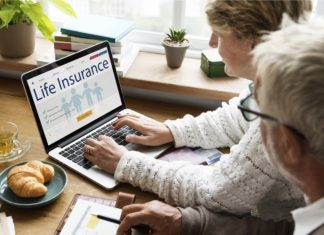 Older Couple Looking At Life Insurance Research Laptop Online
