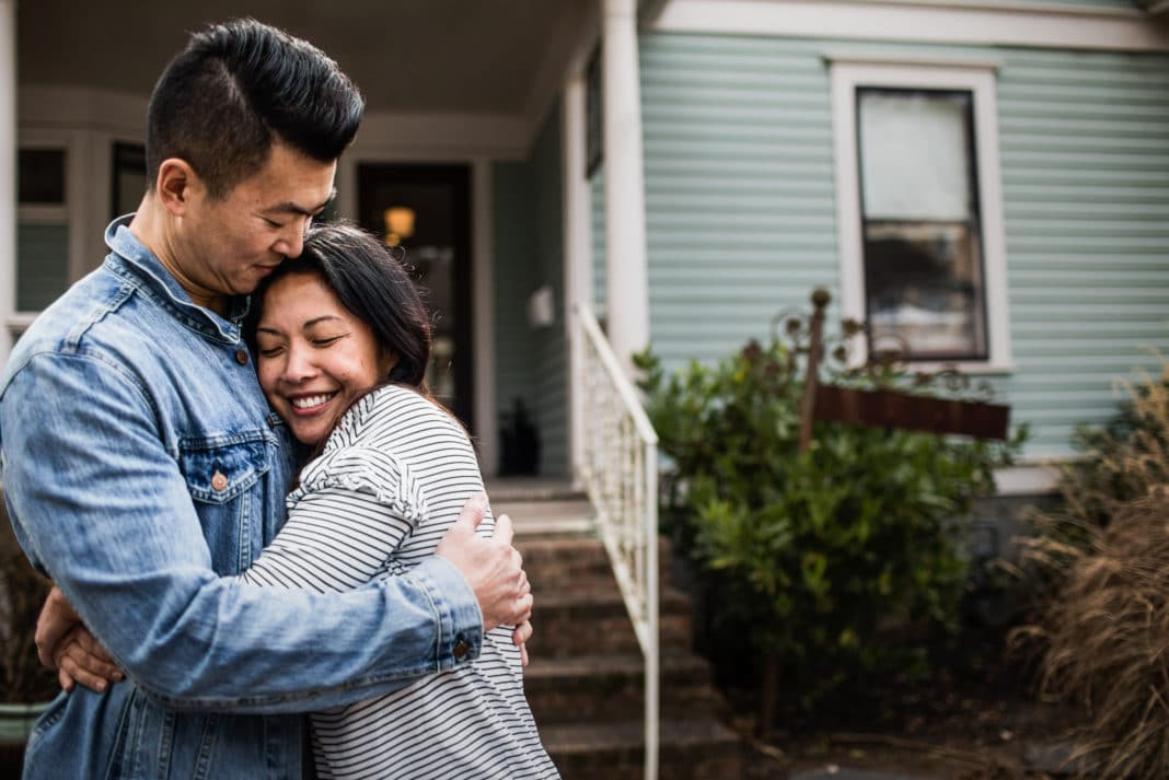 Young Couple Hugging Outside Home