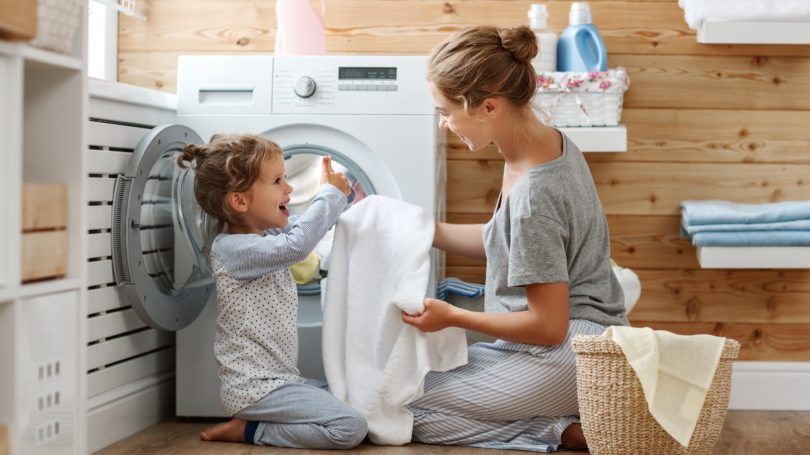 Mother Daughter Doing Laundry Chore Together