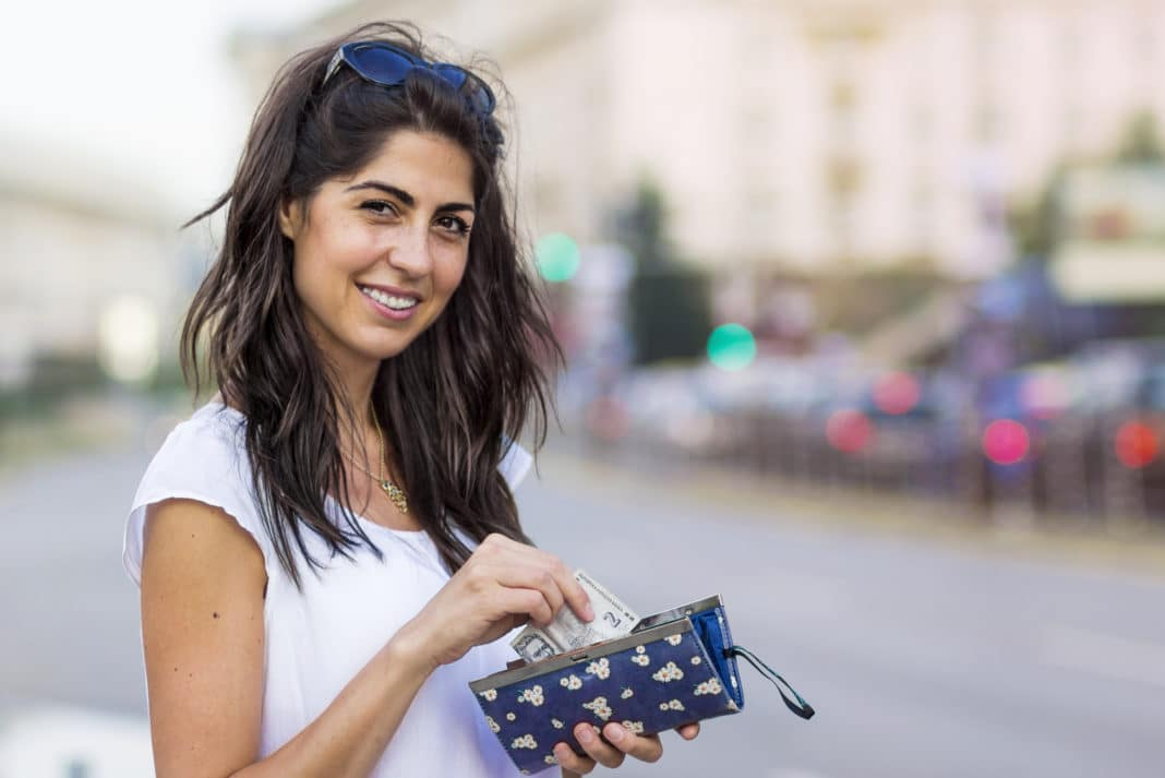 Woman Putting Money Note Into Wallet