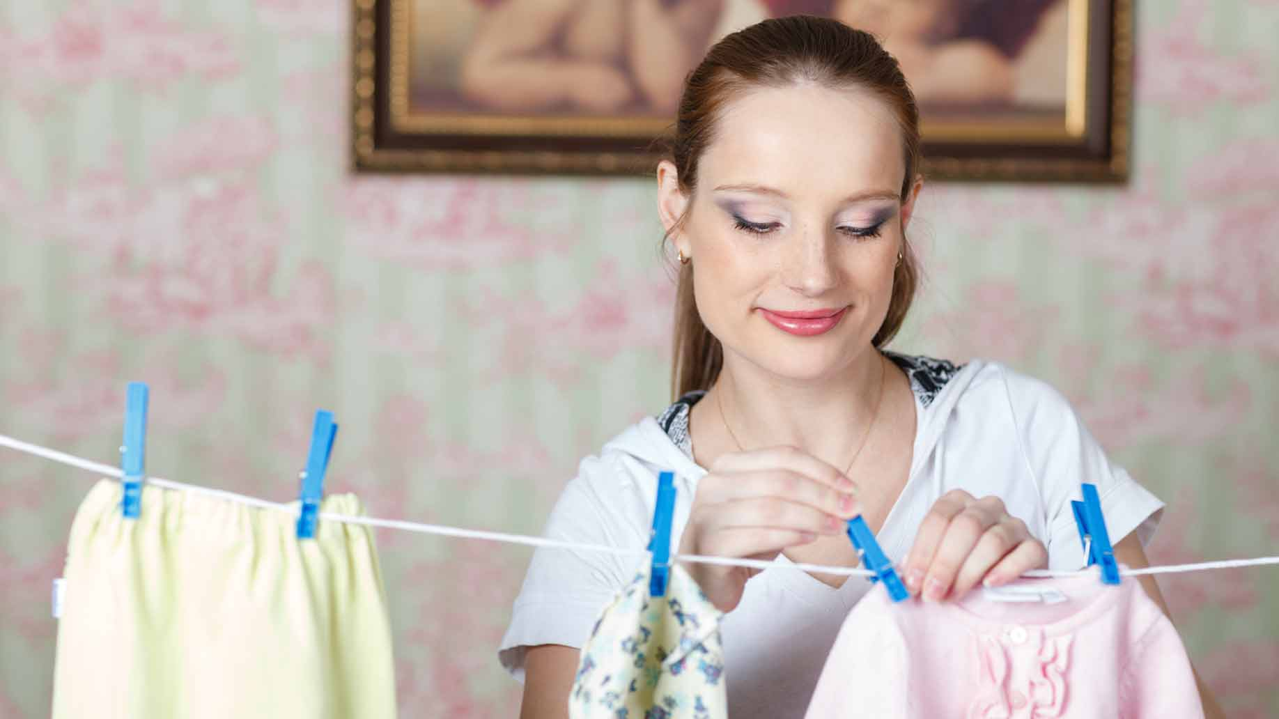 mother hanging baby clothes