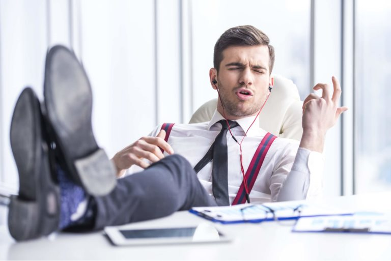Young Man In Suit Listening To Music In Office Doing Air Guitar