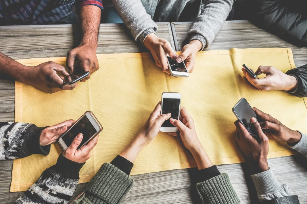 Group Of Friends Smartphones Table On Phone
