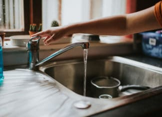 Hand Turning Off Water Facet Kitchen