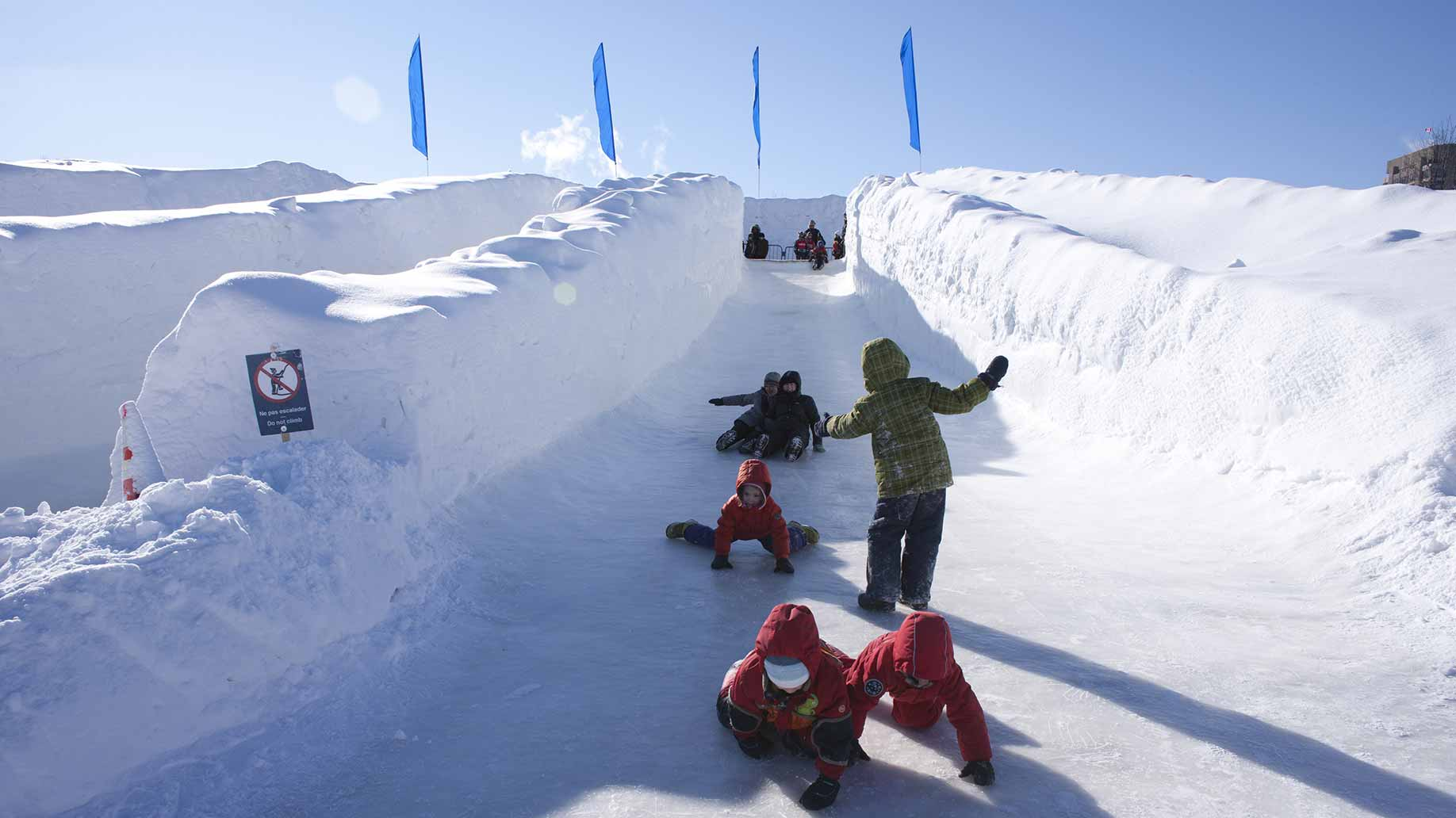 Quebec winter carnival where to stay what to do kids sliding down an ice slide at a winter festival in canada solutioingenieria Gallery