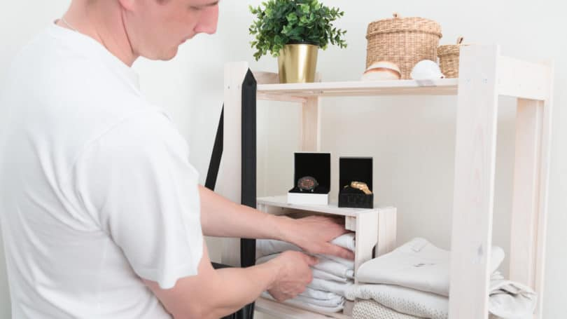 Man Organizing Clothes White Color Scheme