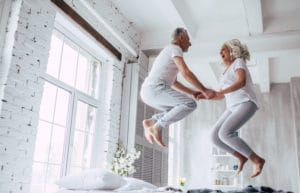Elderly Couple Jumping On Bed White Grey