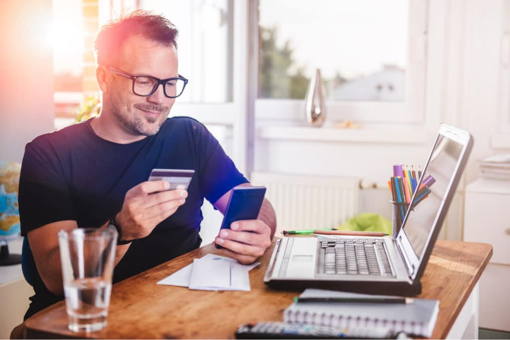 Man Paying Purchase With Credit Card On Phone