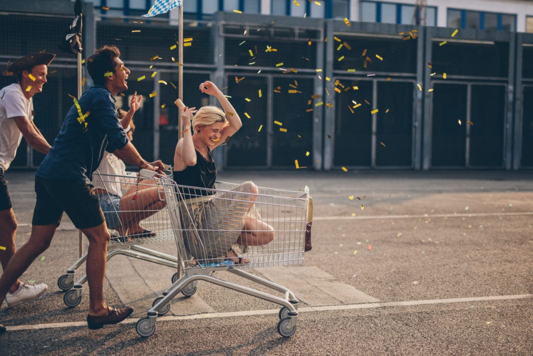 Young Adults Riding Shoppingcarts Celebrating Confetti