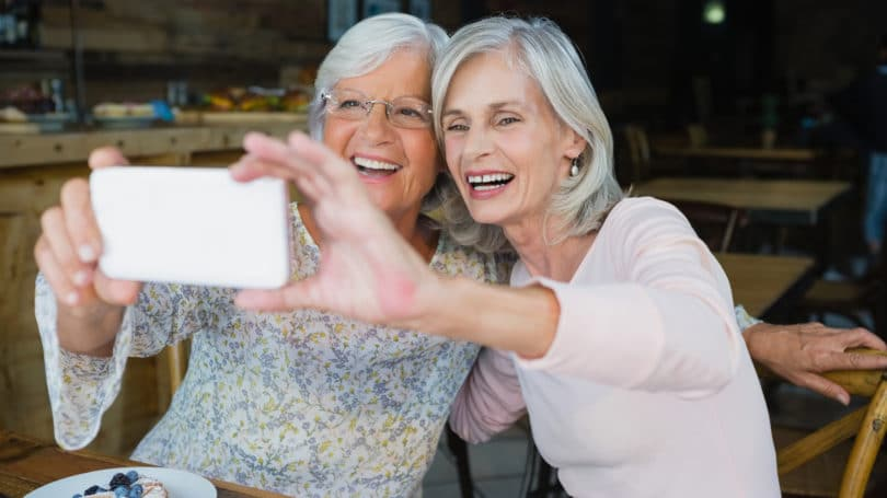 Seniors Grandmothers Eating At Restaurant Taking Selfie