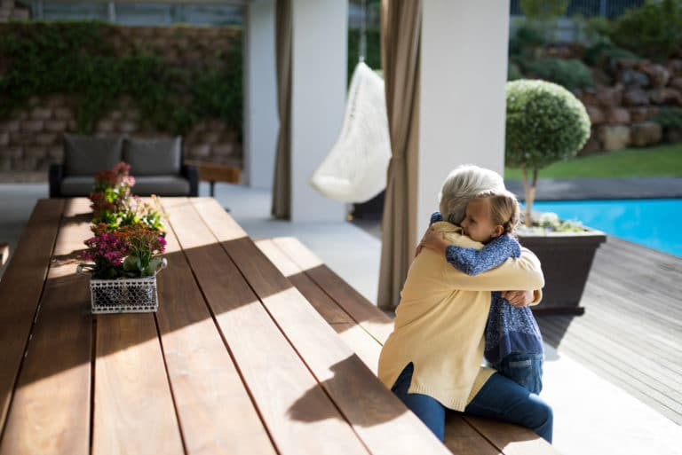 Grandmother Granddaughter Hugging Backyard Outdoors