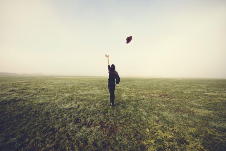 Letting Go Endowment Effect Woman Tossing Hat In Field
