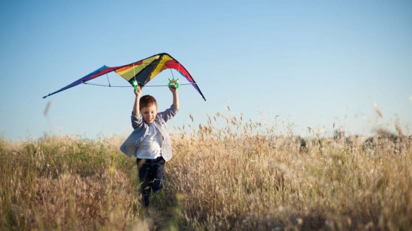 Boy Running With Kite Flying Field Outdoors