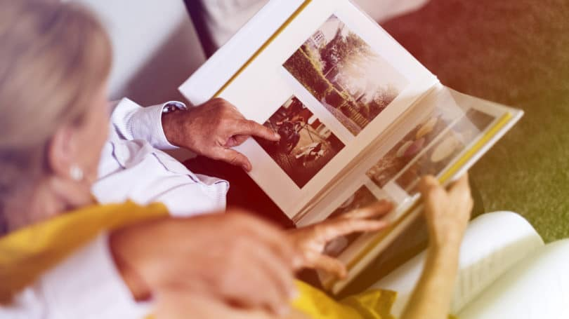 Couple Looking At Old Photos Album