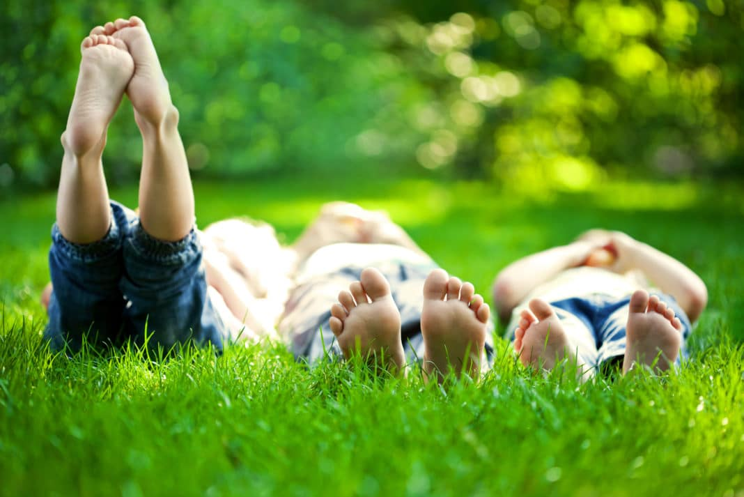 Kids Laying In Grass Barefoot Spring